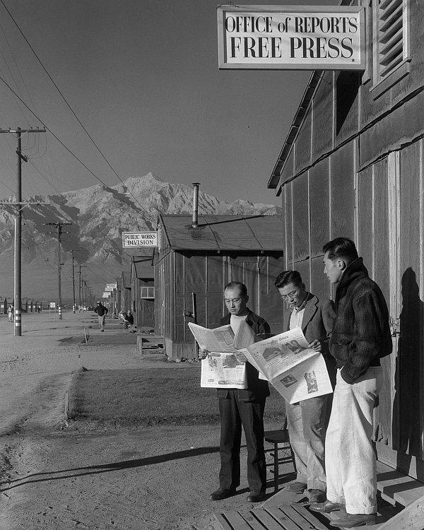 Mężczyźni czytają gazety z których dowiadują się co na wojnie